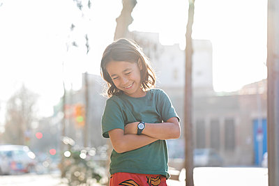 Laughing Young long hair  boy  on the sidewalk - p1166m2096420 by Cavan Images