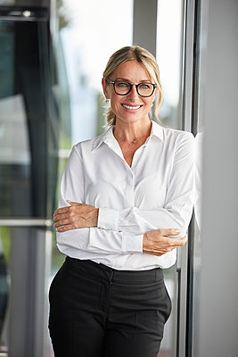 Businesswoman in office leaning against window, with arms crossed - p300m2042951 von Rainer Berg