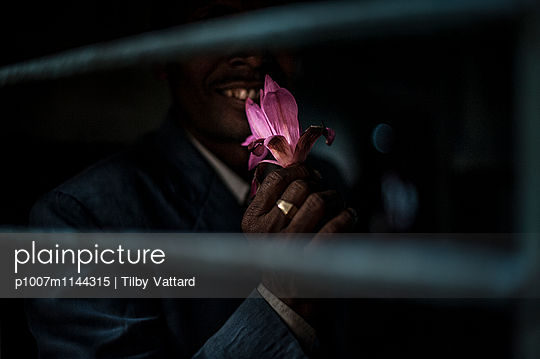 Man smelling a lotus flower - p1007m1144315 by Tilby Vattard
