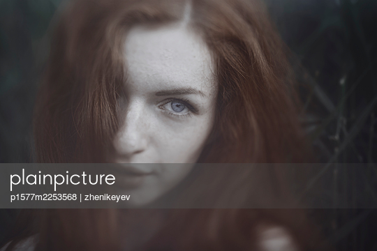 Beautiful redheaded woman outdoors on a greenery background - p1577m2253568 by zhenikeyev