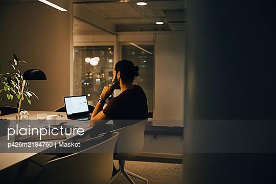Side view of dedicated male professional working late at illuminated desk in coworking space - p426m2194760 by Maskot