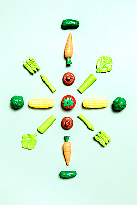 Directly above shot of various vegetable toys arranged on green background - p1094m1467618 by Patrick Strattner