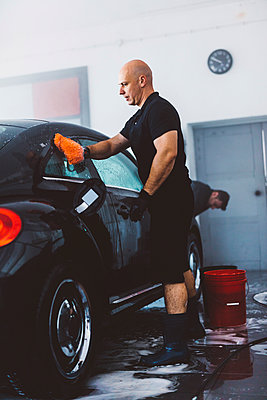 Side view of worker washing car while standing in workshop - p1166m2060369 by Cavan Images
