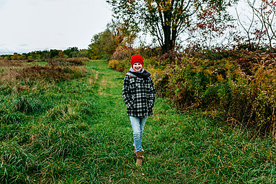 Teenager Walking Down a Country Lane In October in Michigan - p1166m2153346 by Cavan Images