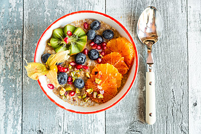 Superfood breakfast with porridge, amaranth, various fruits and pistachios - p300m1356498 by Sandra Roesch