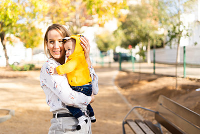Happy mother carrying baby boy in a park - p300m2154771 by Eloisa Ramos