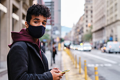 Young man wearing protective face mask using mobile phone while standing in city - p300m2250150 by Alvaro Gonzalez