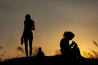 Silhouette women eating and drinking on hill at sunset - p301m2123150 by Tobias Titz