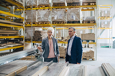 Business people analyzing wooden planks at industry - p426m1537017 by Maskot