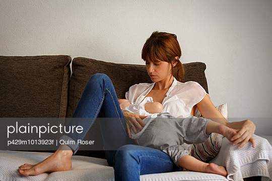 Mid adult woman reclining with sleeping toddler daughter on sitting room sofa - p429m1013923f by Quim Roser