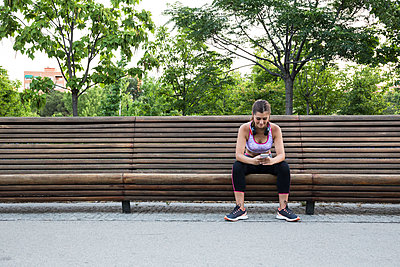 Pretty fit young woman listening to music on park bench. - p1166m2130088 by Cavan Images