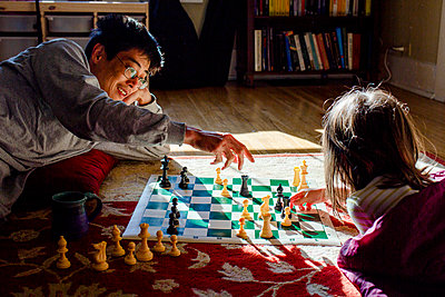 A smiling dad and his young girl play chess in a patch of bright light - p1166m2182931 by Cavan Images