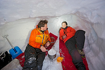 couple melting snow for cooking in snow shelter in Iceland - p1166m2268880 by Cavan Images