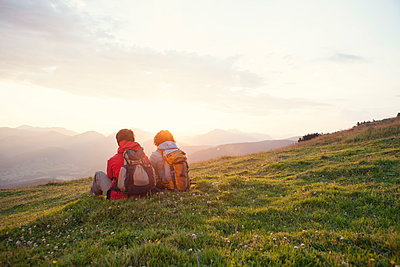 Austria, Tyrol, Unterberghorn, two hikers resting in alpine landscape at sunrise - p300m1188466 by Rainer Berg