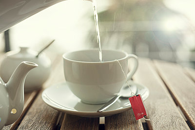 Water being poured into white tea cup - p300m2239997 by LOUIS CHRISTIAN