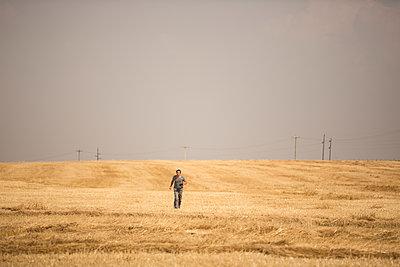 Junger Mann geht über ein Stoppelfeld - p552m1190843 von Leander Hopf