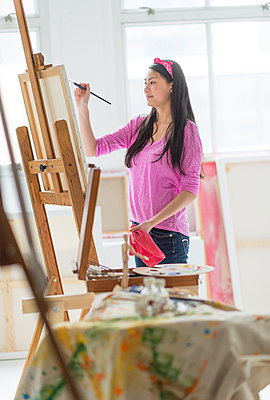 Mixed race teenage girl painting in studio - p555m1415303 by JGI/Tom Grill