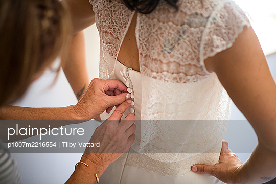 Helping to attach the bride's dress - p1007m2216554 by Tilby Vattard