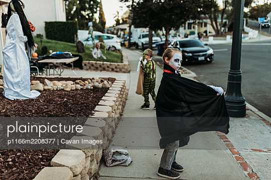 School aged boy dressed as Dracula Trick-or-Treating during Halloween - p1166m2208377 by Cavan Images