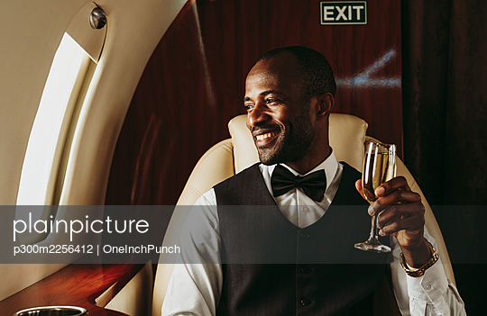 Smiling male entrepreneur holding champagne looking out of window in airplane - p300m2256412 by OneInchPunch