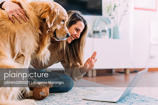 Italy, Young woman with dog looking at laptop - p924m2283021 by Eugenio Marongiu