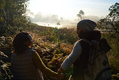 Affectionate young couple holding hands and hiking in nature - p1023m2212947 by Trevor Adeline