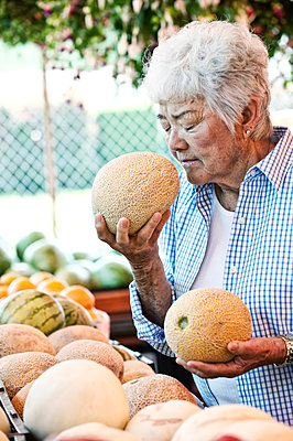 Senior woman standing at a farm stall, holding a fresh melon to her nose, smelling it. - p1100m1575632 by Mint Images