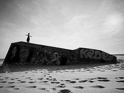 Frau steht auf einem Bunker mit Graffiti - p1150m2211426 von Elise Ortiou Campion
