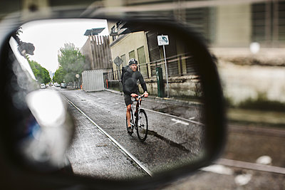 Male commuter riding bicycle on wet street seen through side-view mirror of car - p1166m1417370 by Cavan Images