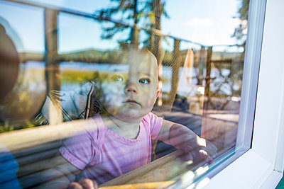 Young girl looking out through window. - p1166m2153369 by Cavan Images