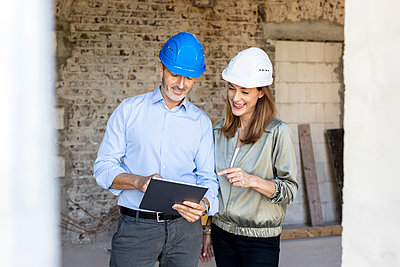 Female client and male architect wearing hardhats while discussing over digital tablet at construction site - p300m2276143 by Peter Scholl