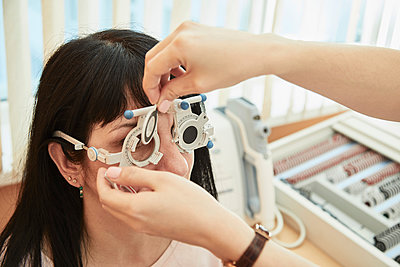 Cropped image of optometrist examining woman's vision at clinic - p301m1579669 by Alexandr Sherstobitov