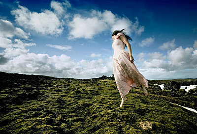 An elfish-like woman soaring over a mossy lava field, Iceland - p34810567 by Rebekka Gudleifsdottir