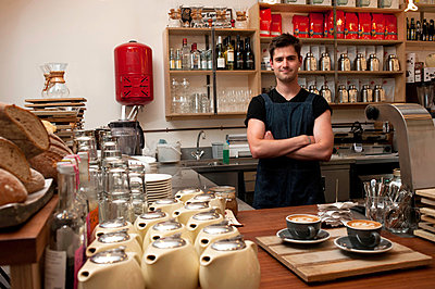 Portrait of young man behind kitchen counter in cafe - p429m824350f by Rogan Macdonald