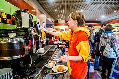 Caucasian woman getting breakfast in cafeteria - p555m1413208 by Aleksander Rubtsov