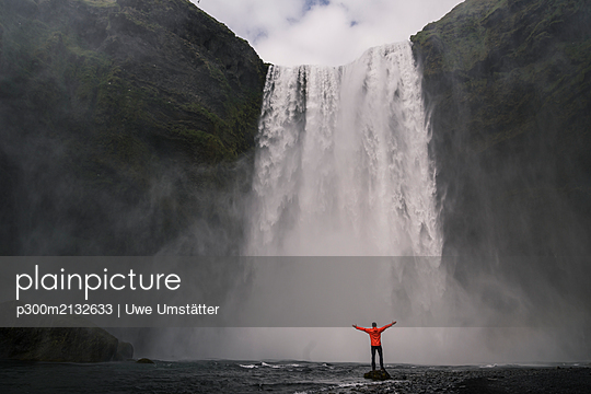 Mature man standing in front of Skogafoss waterfalls with raised arms, Iceland - p300m2132633 by Uwe Umstätter