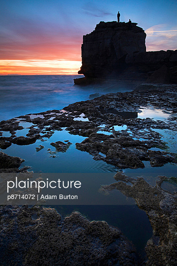 A man stands atop Pulpit Rock watching the sun setting - p8714072 by Adam Burton