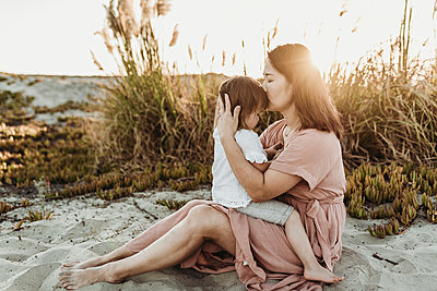 Side view of mother kissing young toddler at beach during sunset - p1166m2165865 by Cavan Images