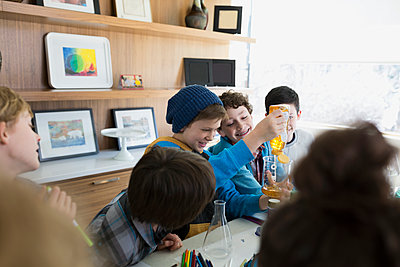 Boys conducting science experiment at dining table - p1192m1129569f by Hero Images
