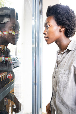 Young African woman looks into a shop window - p1640m2260083 by Holly & John
