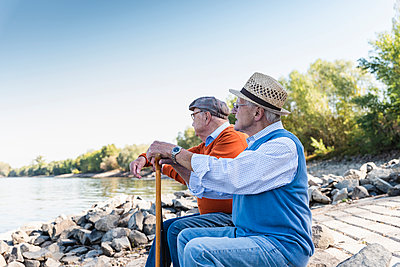 Two old friends sitting on a tree trunk, watching the river - p300m2062729 by Uwe Umstätter