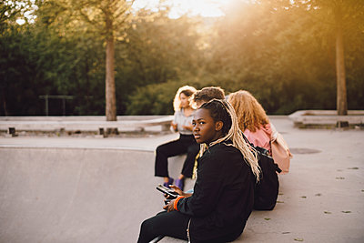Thoughtful teenage girl holding mobile phone while sitting with friends at skateboard park - p426m2072298 by Maskot