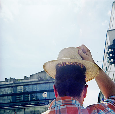 Man Raises Straw Hat On Street At Stockholm  - p847m1529626 by Mikael Andersson
