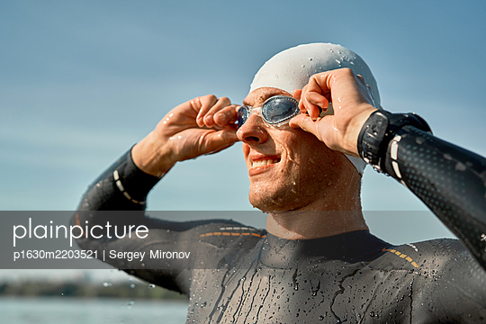 Man puts on swimming goggles while standing on river on summer - p1630m2203521 by Sergey Mironov