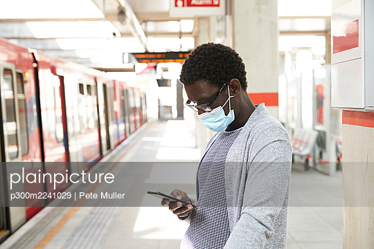 Male commuter wearing protective face mask while using mobile phone at railroad station - p300m2241029 by Pete Muller