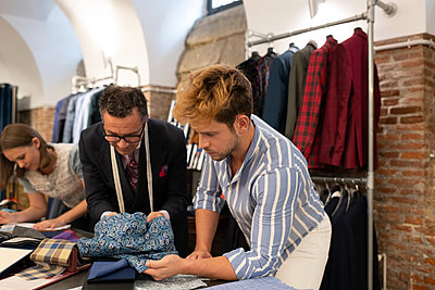 Client and dressmaker selecting cloth - p1166m2261437 by Cavan Images