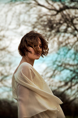 Retro Woman with Windswept Hair by Trees - p1248m1562050 by miguel sobreira