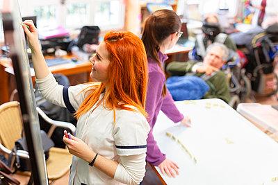 Female volunteer writing on blackboard in rehabilitation center - p300m2243098 by DREAMSTOCK1982