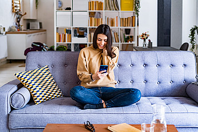 Young smiling woman using mobile phone while sitting on sofa at home - p300m2251530 by Giorgio Fochesato