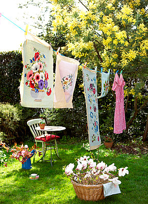 Floral print laundry on washing line in back garden of Isle of Wight home;  UK - p349m920095 by Rachel Whiting